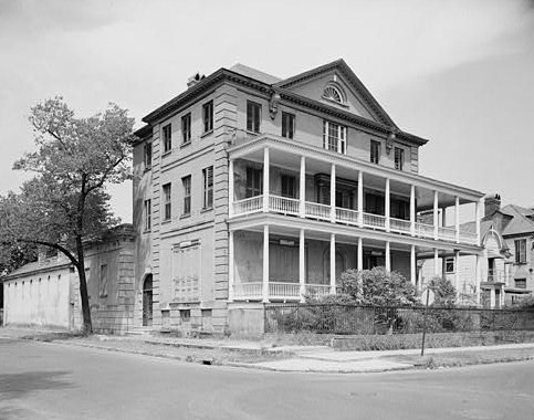 A large, three story home with a two floor porch in the front. The picture is in black and white and taken across the street of the house, with the photo focusing on the corner front view of the home. Not a large front yard, but can slightly view the fenced in backyard