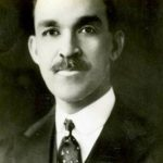 Man faces forward for a portrait. The man is wearing a suit with a designed traditional tie and also has a large mustache, and bushy eyebrows that stand out in the image.