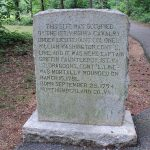 stone monument along a trail in the woods noting the location of a wounded colonel