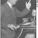 A news strip with a photo of a man making a speech behind a podium. The photo is a side profile off the man with a black background, as he wears glasses and faces upwards along with using hand motions to address his point.