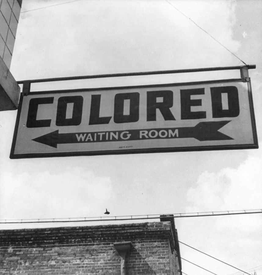 """Sign hanging outside of building that reads """"colored waiting room"""""""