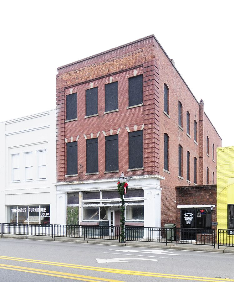 A three story red brick lay building across a street. The building is modeled similar to town buildings, being directly beside two other buildings with no alleyway room.