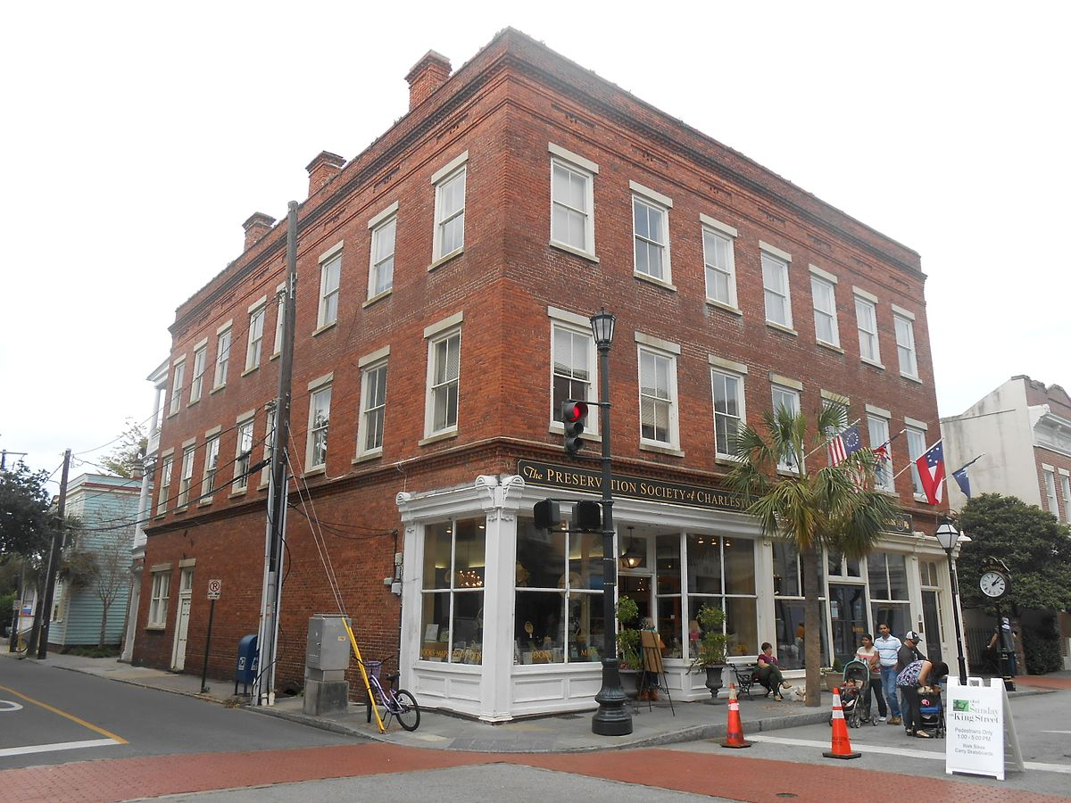 Three Story red brick building on the corner of a street
