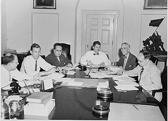 Photograph of members of the Council of Economic Advisers and White House staff members working on the President's Midyear Economic Report in the Cabinet Room