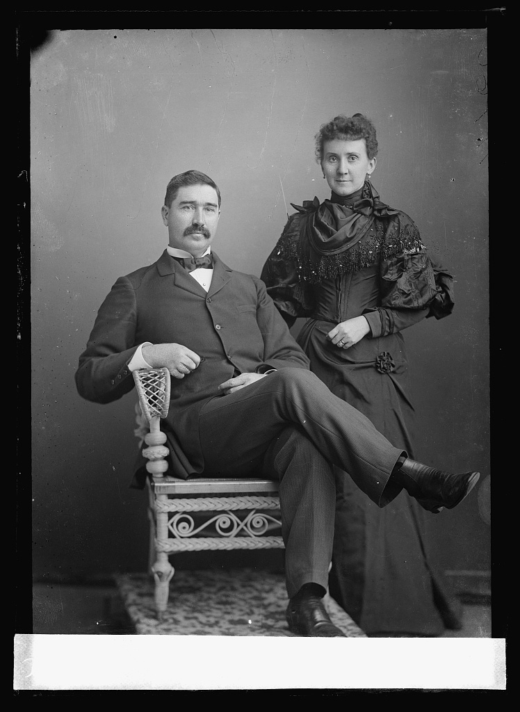 Man sitting for a photo with his wife behind him. They are wearing clothes similar to the victorian era