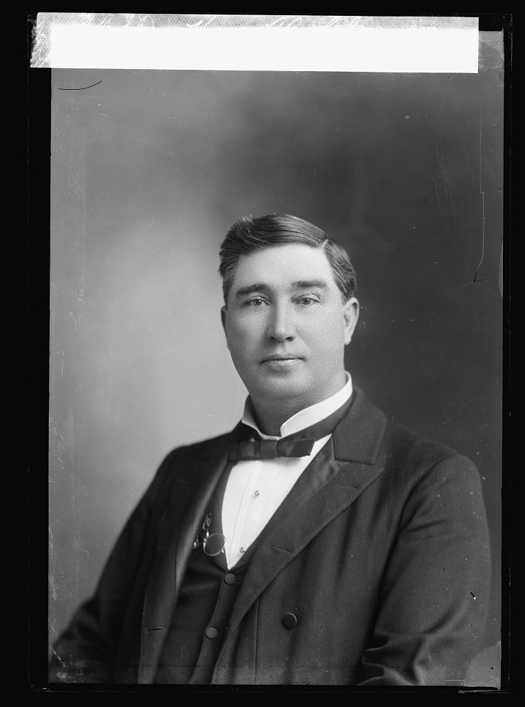 Young man posing for a photograph, in a suit and looking sternly