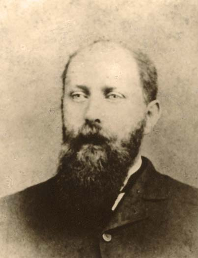 yellow faded portrait of a man facing forward. He is slightly bald and has a long straggly beard which extends to the neck of his black suit jacket.